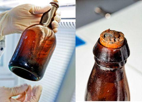 Finger, Brown, Fluid, Bottle, Amber, Liquid, Glass bottle, Nail, Maroon, Serveware,