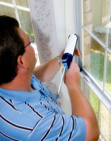 man caulks around a window