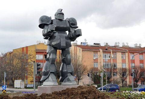 Sculpture, Mecha, Monument, Statue, Machine, Street light, Parking, Robot, Mid-size car,