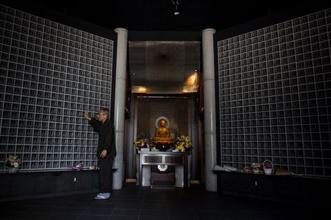 TOKYO, JAPAN - APRIL 06:  Koukokuji temple head priest Yajima Taijun looks at the unlit glass buddha statues at the Ruriden columbarium on April 6, 2015 in Tokyo, Japan. The Ruriden, operated by the Koukokuji buddhist temple, took two years to build and houses 2046 futuristic alters with glass buddha statues that correspond to drawers storing the ashes of the deceased. An IC card allows the owner of the alter to access the building and lights up the corresponding statue. The ashes are stored for 33 years before being buried below the Ruriden, currently 600 alters are in use and another 300 are reserved.  (Photo by Chris McGrath/Getty Images)
