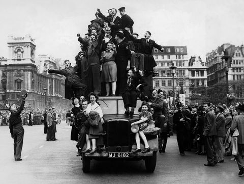 VE Day celebrations in London with cheering crowds and servicemen on the streets and hanging onto a truck, 8th May 1945.  (Photo by Popperfoto/Getty Images)
