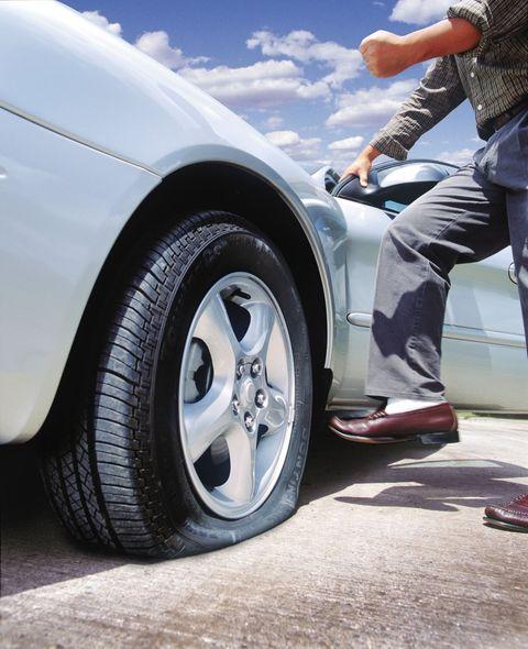 Man kicking flat tire on car