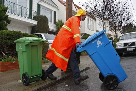 A Recology employee does recycling and trash pickups in San Francisco