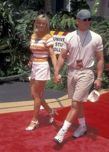 """90210's Ian Ziering, t-shirt tucked into beltless same-color shorts, shows calm in the face of a theme-park water-storm, plants seed for future """"Sharknado"""" comeback, brings spare ball cap. Wife Nikki Schieler wears Hooters Air flight attendant uniform prototype."""