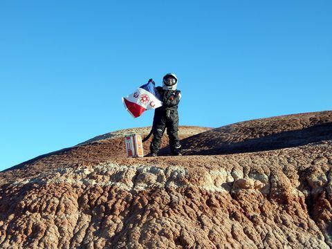 Kellie Gerardi carries The Explorers Club flag to Mars.