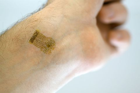 Photograph of the epidermal device placed on skin above a blood vessel.