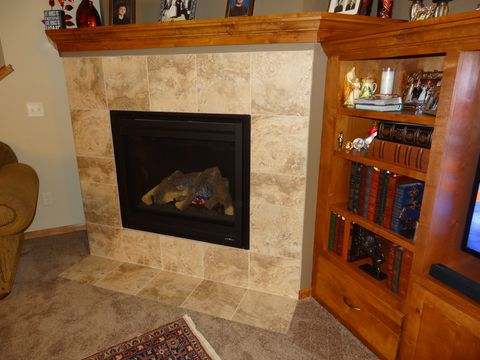 Hearth, Flooring, Floor, Wood stain, Fireplace, Carpet, Shelving, Shelf, Heat, Interior design,