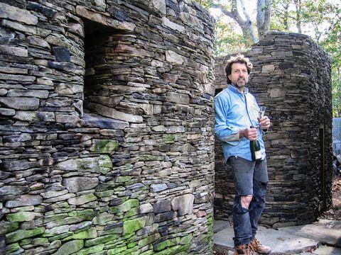 Human, Denim, Jeans, Wall, Brick, Stone wall, Trunk, Street fashion, Brickwork, Cobblestone,