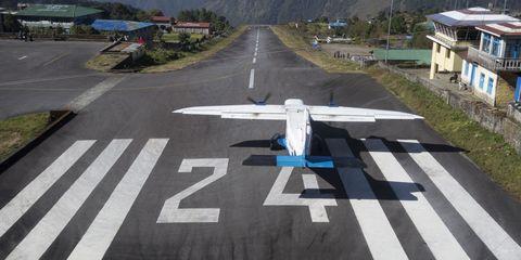 Airplane, Aircraft, Runway, Road, Road surface, Aviation, Asphalt, Mountain range, Aerospace engineering, Lane,