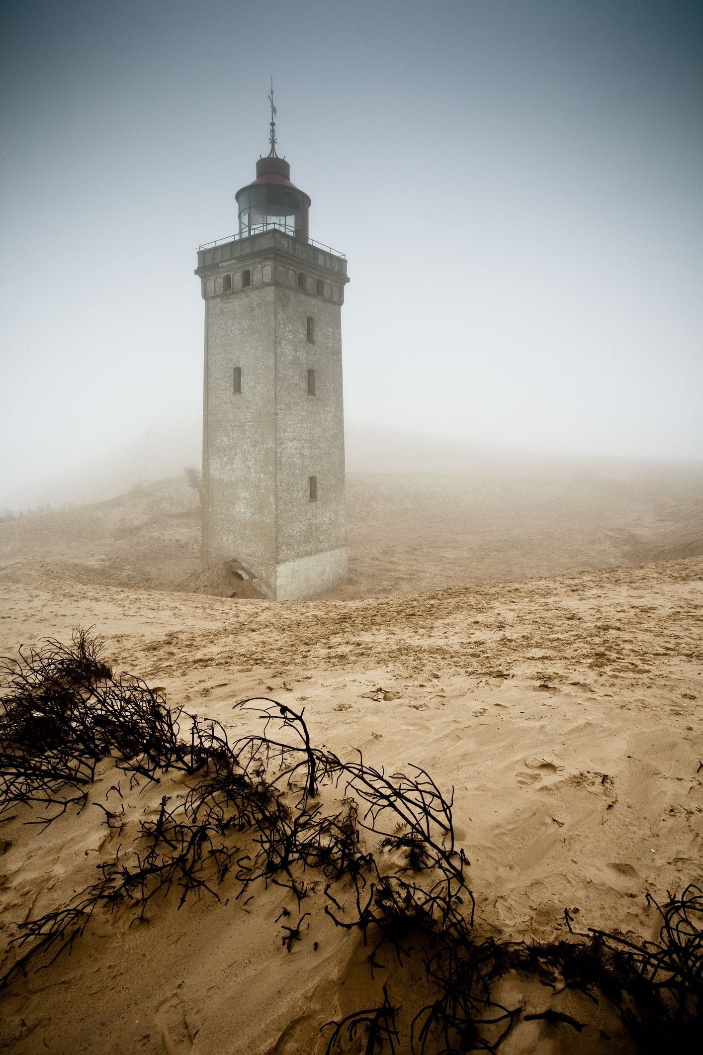 <p>When it became clear that if the sand dunes didn't completely engulf thiscentury-old structure first, it would eventually topple into the North Sea due to coastal erosion, the lighthouse was left to the elements. It is located on the northern coast of Denmark.</p>