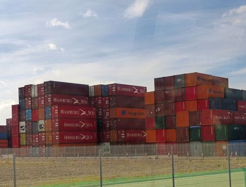 "<p>Every shipping container in the world has its own unique 20-digit identification number, known as a box number.  Although containers are always expressed in terms of ""Twenty-Foot Equivalent Units"" or TEU, <a href=""http://www.worldshipping.org/about-the-industry/containers"">the most common type of container is the 40-foot version</a>, which is exactly the same size as two TEUs end-to end.</p><p><br></p><p>The standard container is a simple steel or aluminum metal box, but specialized containers include <a href=""https://www.cma-cgm.com/static/Communication/Attachments/CMACGM_Containers_17_02_2014_web.pdf"">bulk liquid containers</a> and <a href=""https://www.cma-cgm.com/products-services/reefer/containers-fleet"">refrigerated units</a> or ""reefers"" used for fresh fruit or frozen produce with controls for atmosphere as well as temperature. But many of the containers at the port at any given time are empties, waiting to be returned on the next ship.<span data-redactor-tag=""span""></span></p>"