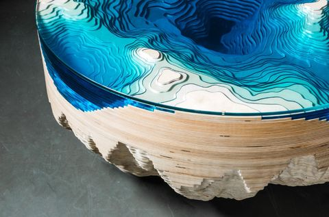 <p>The table is designed to look like a bathymetric map of the seafloor, using layers of wood and glass. The wood and glass are cut with millimeter precision and fitted together, and the layers are compressed together with an airtight seal.</p>