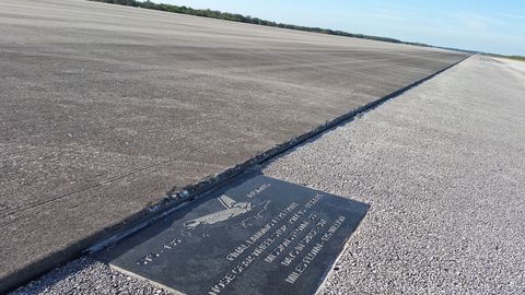 <p><span>The Shuttle Landing Facility is&nbsp;simply massive—15,00 feet long and 200 feet wide, with two feet of concrete at its the center. It can accommodate some of the largest aircraft in the world as well as spaceplanes traveling at high speeds. There are two wide asphalt drive lanes on either side of the concrete. The lip between the two are evident near this plaque commemorating the final shuttle mission.</span></p>