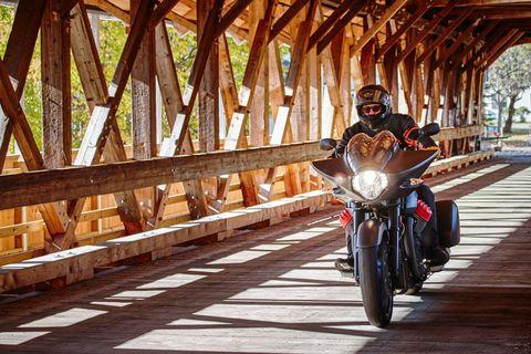Motorcycle, Tire, Wood, Automotive tire, Automotive lighting, Motorcycle helmet, Motorcycling, Fender, Helmet, Headlamp,