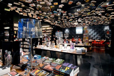 """<p><a href=""""http://www.cookandbook.be/"""" target=""""_blank"""" data-tracking-id=""""recirc-text-link"""">This bookshop in Brussels</a> features an eye-catchinginstallation of tomes suspended from the ceiling that seem to be flying likebirds—and that's just one facet of its exuberant design. Visitors will alsofind a vintage Fiat 500 parked in the café and Union Jacklamps in theEnglish section.</p>"""