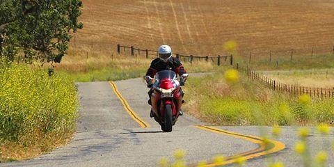 Clothing, Motorcycle, Road, Motorcycle helmet, Motorcycling, Infrastructure, Helmet, Fender, Road surface, Asphalt,