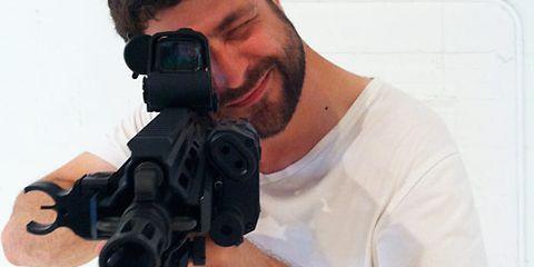 Elbow, T-shirt, Cool, Facial hair, Beard, Optical instrument, Cameras & optics, Gunshot, Top, Revolver,