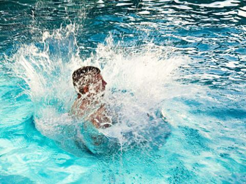 man cannonball diving into pool