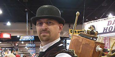 Hat, Facial hair, Sun hat, Fedora, Belt, Brass, Horse tack, Costume hat, Market,