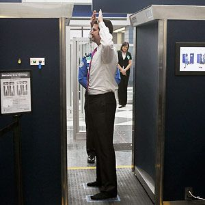 A TSA volunteer demonstrates a full-body scanner at O'Hare International Airport.
