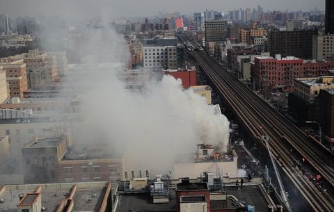 New York City Fire Department firefighters at the scene of an explosion and building collapse at Park Avenue and East 116th Street March 12, 2014 in the Harlem section of New York.
