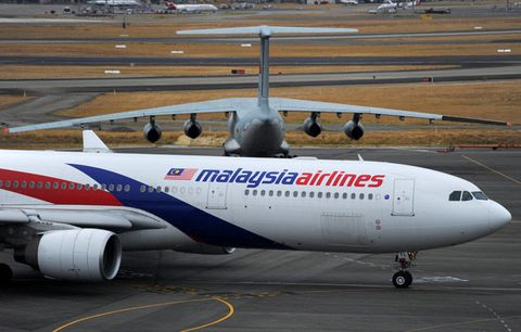 PERTH, AUSTRALIA: A Malaysia Airlines plane prepares to go out onto the runway and passes by a stationary Chinese Ilyushin 76 aircraft (top) at Perth International Airport on March 25.