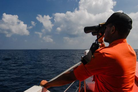 An Indonesian National Search and Rescue Agency personnel scans the seas aboard a boat on patrol in the Malacca Strait off Aceh province located in the area of northern Sumatra island on March 12, 2014 during the continued search for the missing Malaysia Airlines flight MH370.