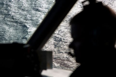 Captain Peter Moore is silhouetted against the southern Indian Ocean aboard a Royal Australian Air Force AP-3C Orion aircraft searching for missing Malaysian Airlines flight MH370, on March 27.