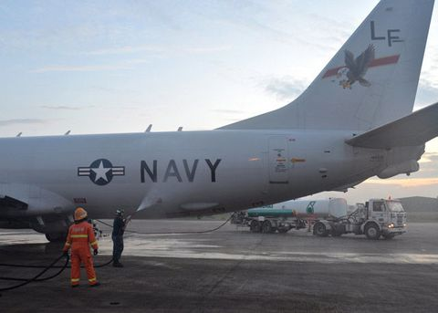 U.S. Navy Aviation Structural Mechanic 2nd Class Matthew Walton sprays down a P-8A Poseidon with before its flight to assist in search and rescue operations for MH370.