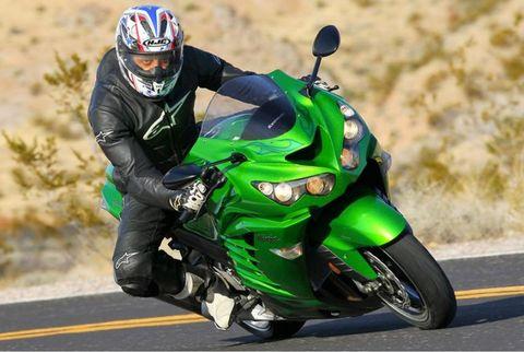 Motorcycle, Motorcycle helmet, Automotive design, Motorcycling, Vehicle, Land vehicle, Green, Motorcycle racing, Automotive tire, Sports gear,