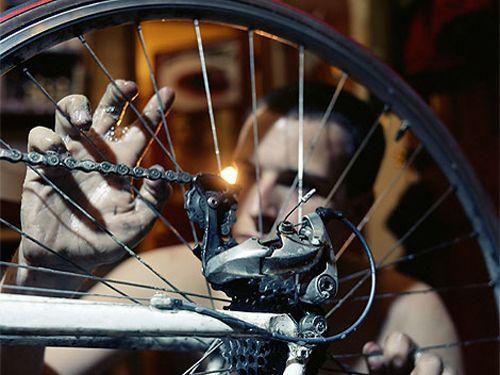 Man Inspecting Bike Wheel