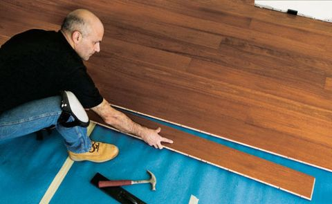 This floating floor is installed over a thin foam rubber pad. The 6-ft.-long planks lock together with tongue-and-groove joints.