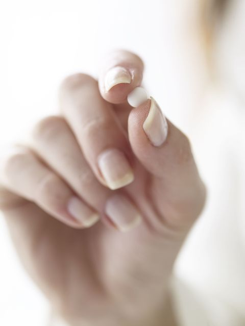 Female hand holding small pill