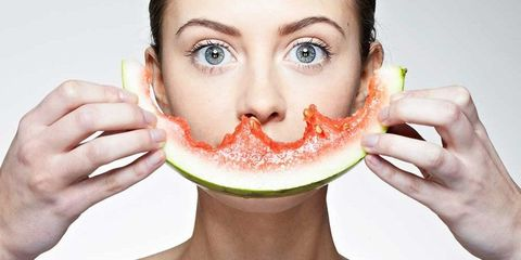 Woman holding watermelon over mouth