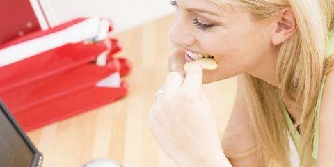 Woman eating crisps at desk