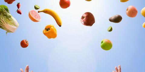 Fruit and veg falling towards hands