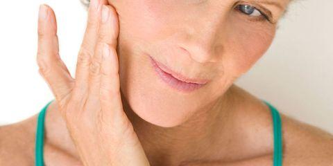 Mature woman applying face cream