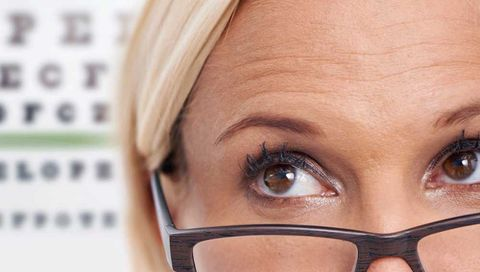Woman with glasses looking at an eye test