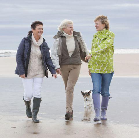 Happy women walking on the beach