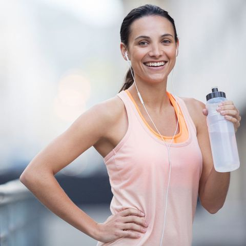 woman runner drinking from a water bottle