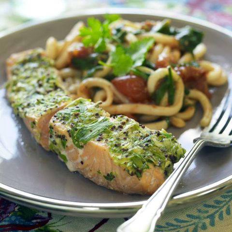 Salmon topped with a green sauce and with noodles and vegetables