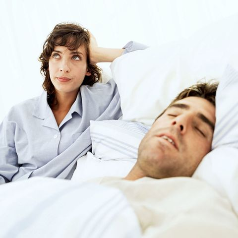 Woman annoyed with snoring man in her bed