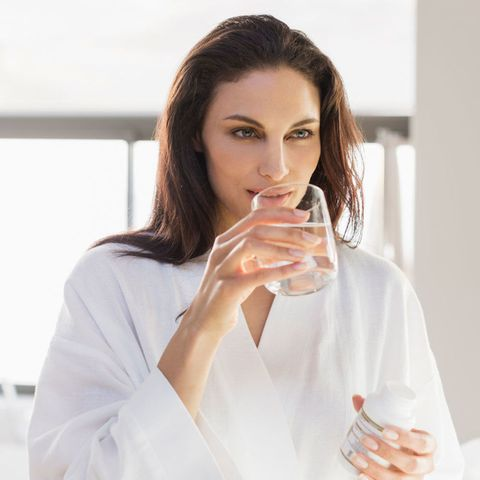 Woman drinking a glass of water and holding a tub of vitamins
