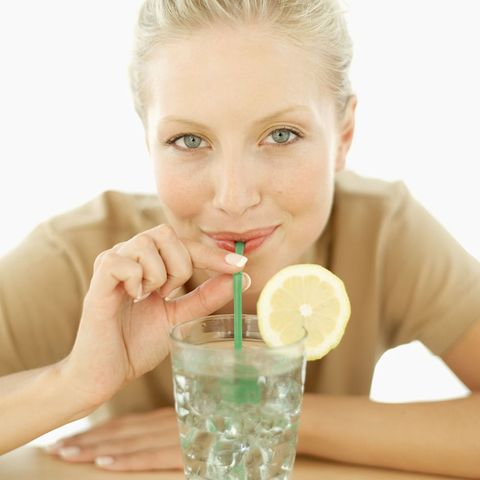 Getty woman drinking water with straw