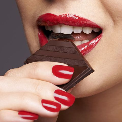 Woman biting piece of chocolate