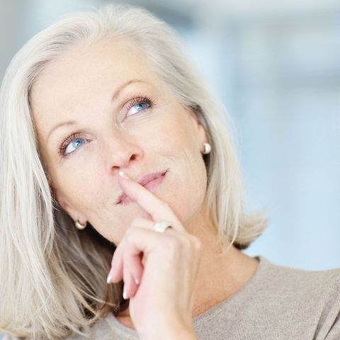 Mature woman, finger on mouth, looking up