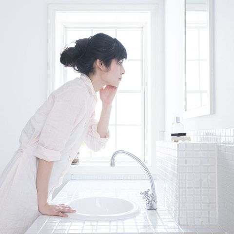 Japanese woman touching her face.