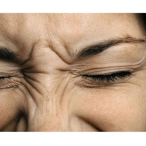 Woman with migraine screwing up eyes
