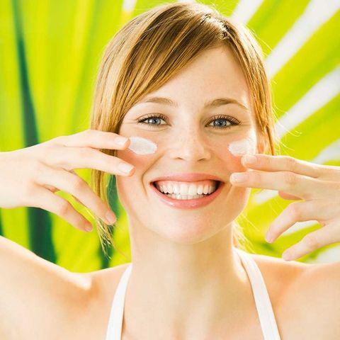 Happy woman putting on sunscren