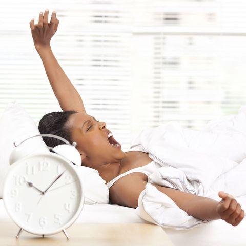 Woman yawning, with alarm clock